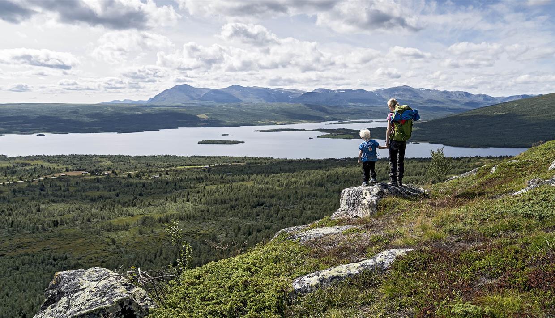 Kvinne og barn står på liten stein og skuer utover et storslått landskap, med innsjø og fjell i bakgrunnen.