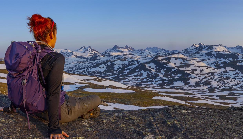 Eine Frau sitzt im Vordergrund und genießt die Aussicht zum Hochgebirge mit vielen Schneefeldern im lila Morgenlicht.
