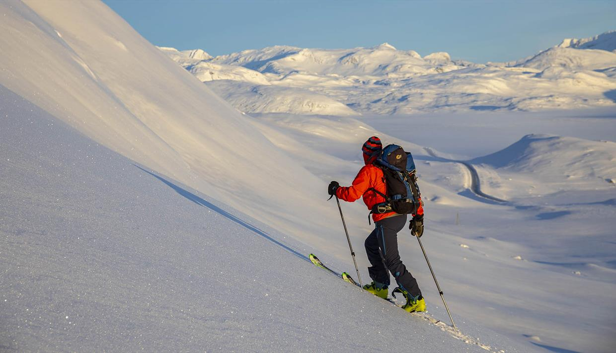 Person on the way upwards with randonee skis, great view over the snow covered mountain landscape.