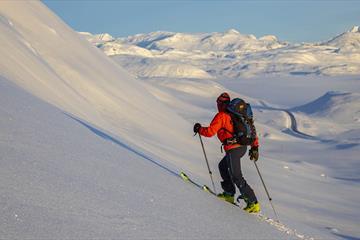 Person på vei opp fjellside med randoneeski, vid utsikt over snødekt fjellandskap
