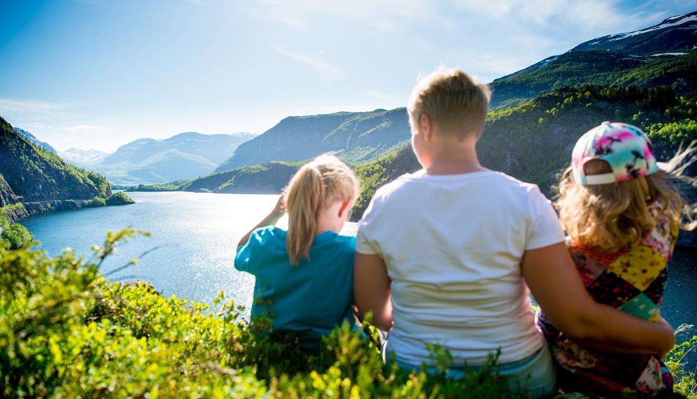 Eine Familie sitzt im Gras in einem Hang und schaut über einen See, der von Bergen umgeben ist.