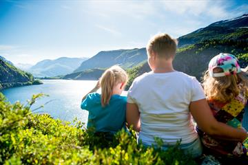 A family sits in a hillside and enjoys the view over a lake surrounded by mountains.