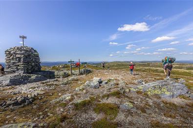 En stor steinvarde og folk på vandretur på toppen av Bjørgovarden
