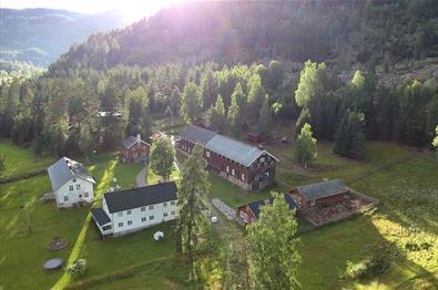 Dronebildet av gården ovenfra med flere bygg, store plenarealer og tilgrensende skogsholt, og solstråler som skaper lys og skygge.