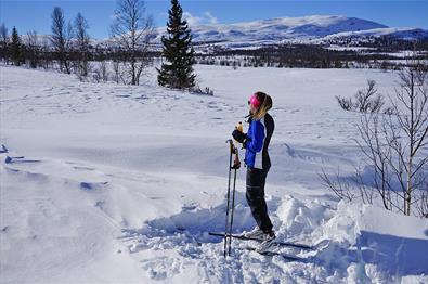 Eine Skiläuferin genießt eine Brause in der Frühlingssonne im Loipennetz bei Kvålestølen. Ein Berg im Hintergrund.