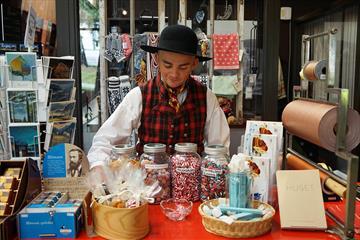 En bunadkledd ung mann bak disken på en museumsbutikk med gammeldagse drops på glass, strikkede votter, kunstkort og bøker.
