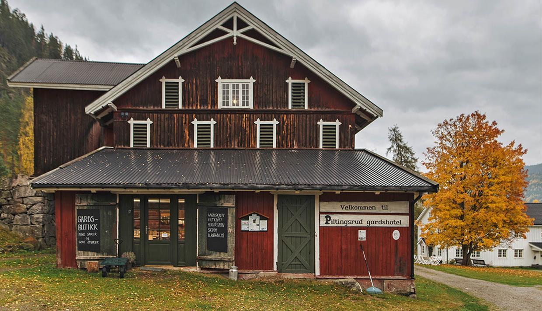 En gammel gårdsbygning med en gårdsbutikk, gressplen, en grusvei og et høstgult lønnetre.