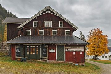 An old farm building with a farm store, a lawn, driveway and a yellow, autumn-coloured maple tree