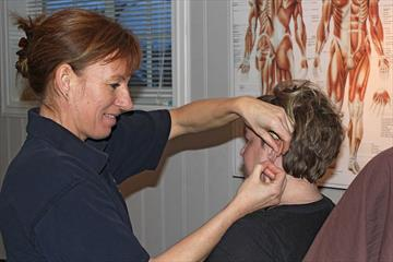 A therapist is giving acupuncture to a patient.