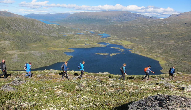 Wanderer in einer Reihe im baumlosen Fjell. Seen liegen im Hintergrund.