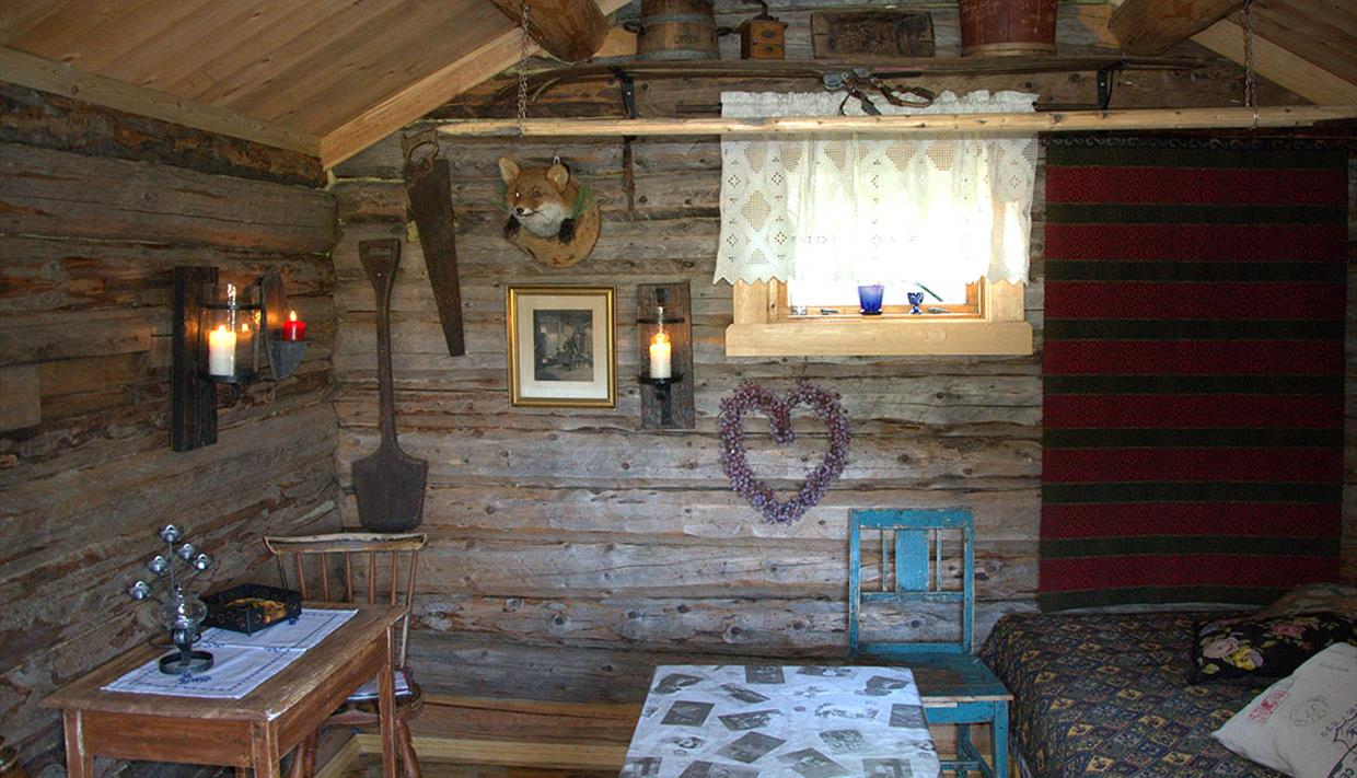 The bedroom of an old timber cabin with bare log walls.