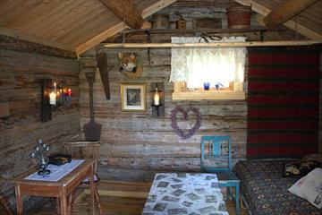 Soverommet på stabburet på Kjeldeskogen, med nakne laftete vegger i gammel bondestil.