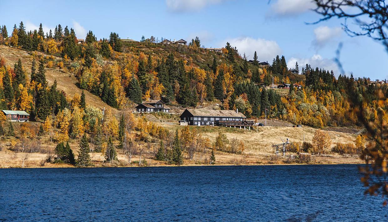 Gamlestølen ligger flott til med fiskevann rett nedenfor, og fjellterreng bak fjellstuen.