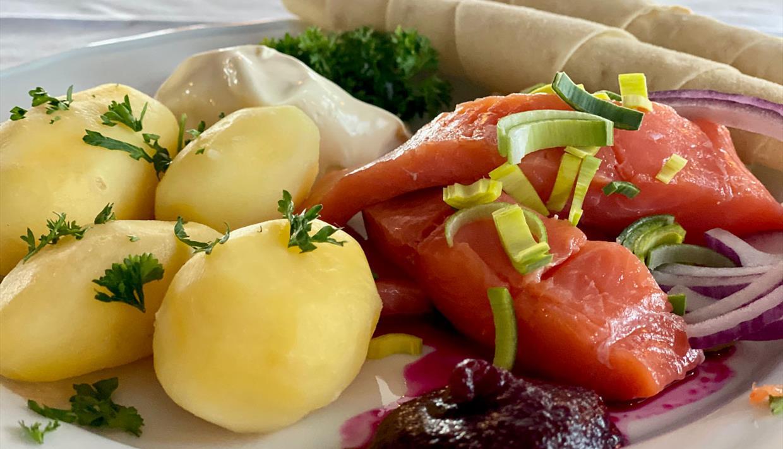 Rakfischteller mit gekochten Kartoffeln, Rakfisch und Beilagen