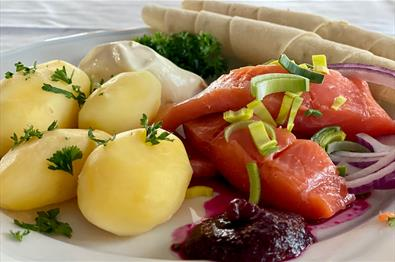 Rakfisk plate with boiled potatoes, semi-fermented trout and sides
