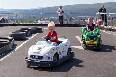 Barn i små elektriske biler på asfaltbane på beitostølen.