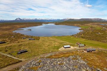 """Aussicht vom Valtjernknatten über den See Valtjern und die Hochebene Stølsvidda. Die Fahrradtour """"Stølsviddarunde"""" verläuft auf der Straße unterhalb der Anhöhe."""