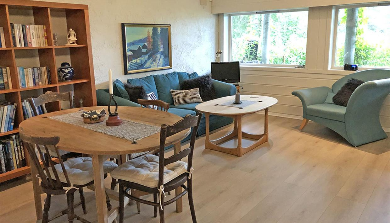 Image of the living room with a dining table for four, a sofa and an arm chair.