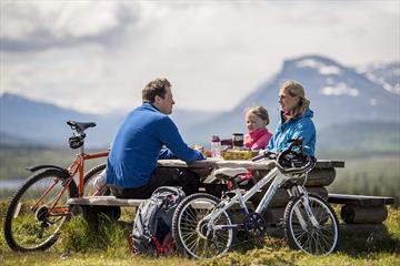 Familie på sykkeltur tar en rast ved en benk. Fjerlli bakgrunnen.