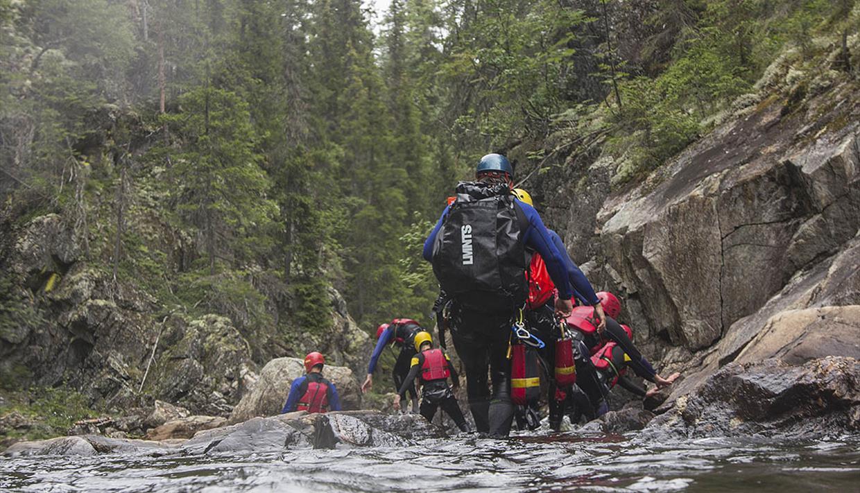 Eine Gruppe in Neoprenanzügen und Helmen geht in einem Fluss.