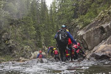 En gruppe personer i våtdrakter og hjelmer går i en elv.