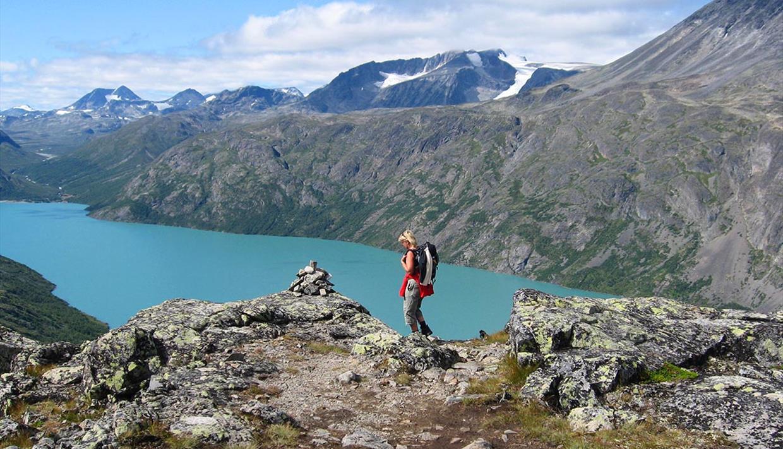 Dame på fjelltur over en fjellrygg over bregrønt vann
