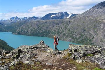 Female hiker on a ridge overlooking a turqoise lake