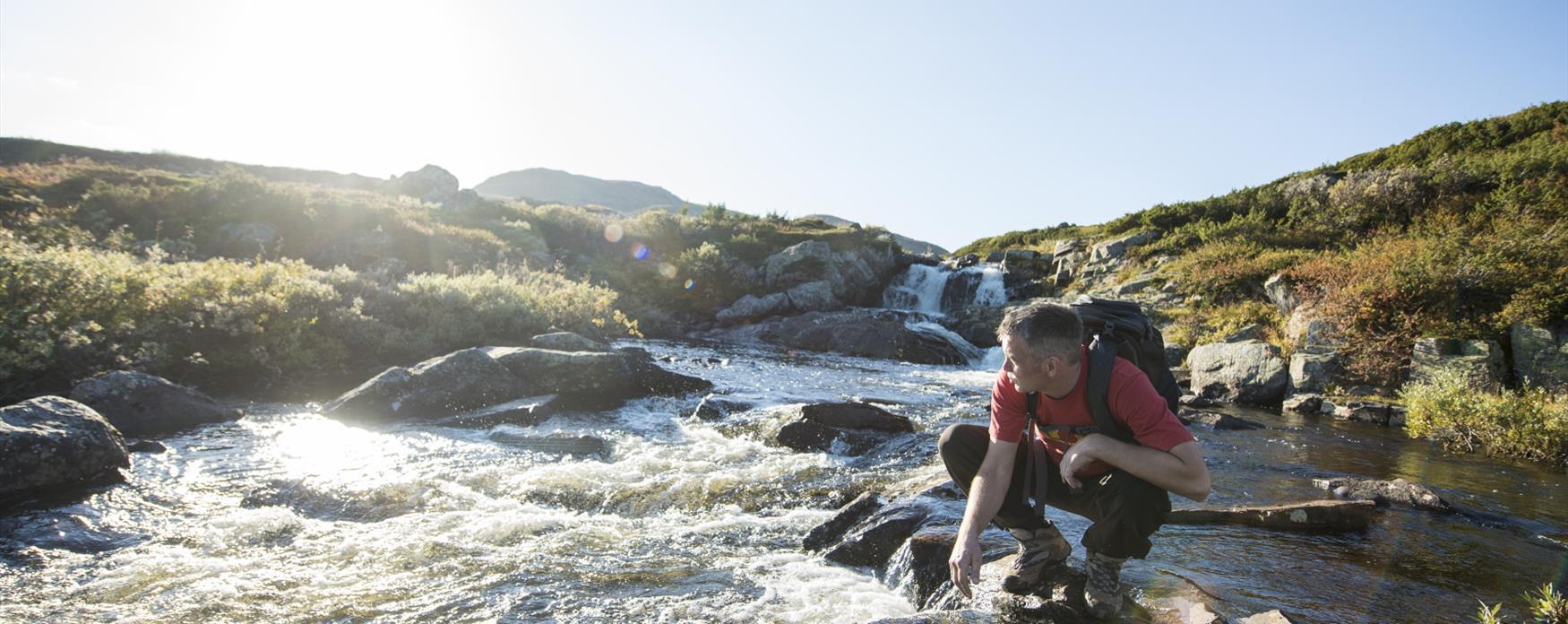 Mann som drikker vann fra elva