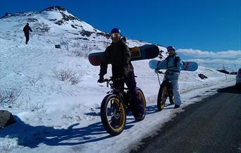 Sykling med snowboard på ryggen