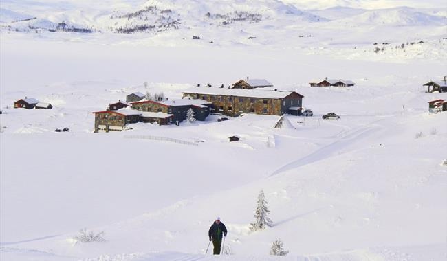 Turist i skiløypa med Rødungstøl Høygfjellshotell i bakgrunnen.