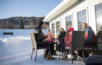 Familie på 5 koser seg utenfor campingvogn, i flott vintervær.