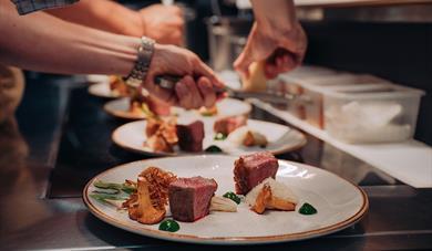 kokker på restaurant Jacob & Gabriel legger mat på tallerken