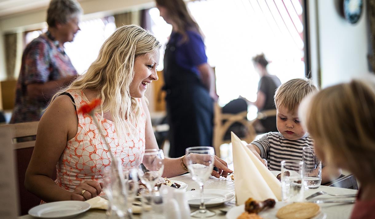 mor og barn sitter på restaurant på Straand Hotel