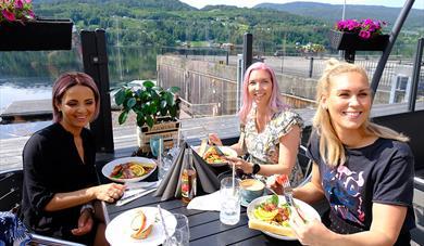 Tre kvinner spiser mat og koser seg på uteserveringen til Dany's Café i Bok & Blueshuset i Notodden. Foto