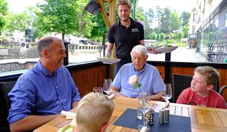 En familie får servert mat på uteserveringen til EYDE Bar & Restaurant i Notodden. Foto