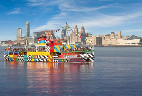 The Mersey Ferries brightly coloured Dazzle Ferry sailing on the Mersey River on a blue sky day. The iconic Liverpool skyline is behind the ferry.