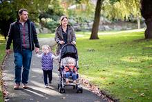 A man and woman hold hands with a young child. The Mother is also pushing a younger child in a pushchair. They are walking through a park.
