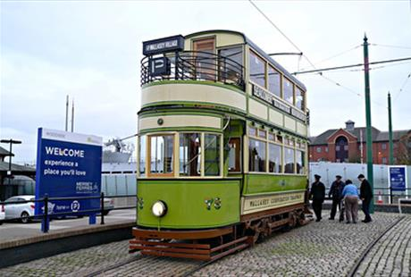 A vintage green tram attached to the original tramlines outside of the museum.
