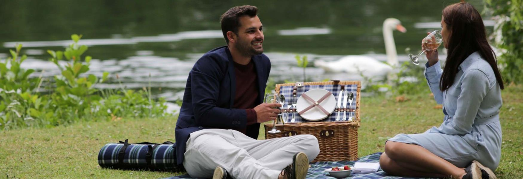 Two people enjoying a picnic by the River Thames at Runnymede