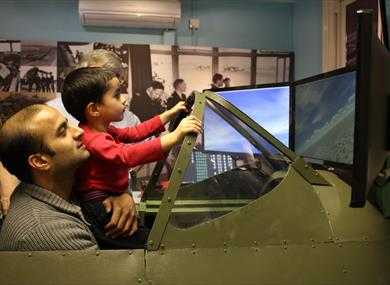 Maidenhead Heritage Centre: man and boy enjoying the Spitfire Simulator