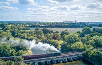 The Royal Windsor Steam Express with Windsor Castle in the distance