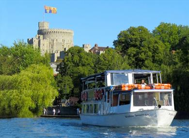 French Brothers boat on the River Thames with Windsor Castle in the distance