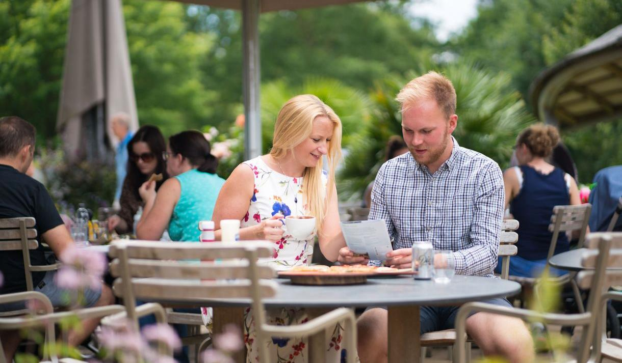 Visitors looking at the menu on the terrace of The Savill Garden Kitchen