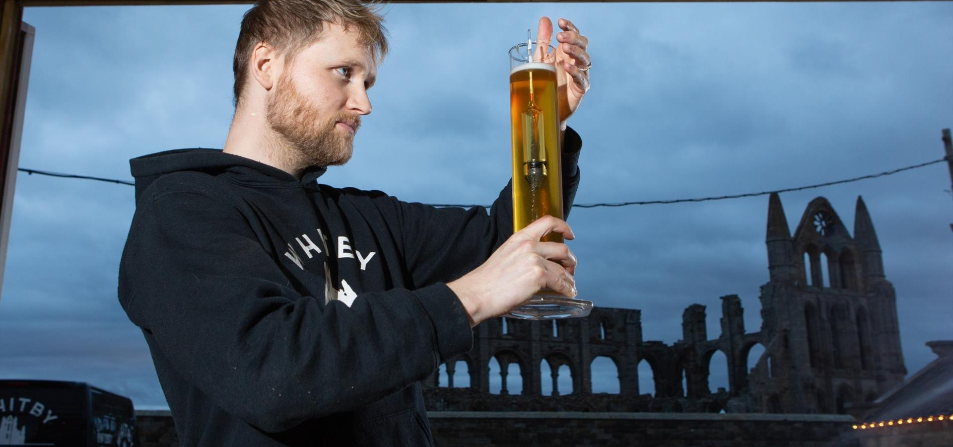 An image of a man holding a beer at Whitby Brewery with Whitby Abbey in the background by Duncan Lomax