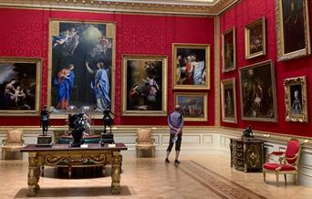 Man looking at painting in an opulent room
