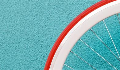 Bicycle wheel against a bright wall