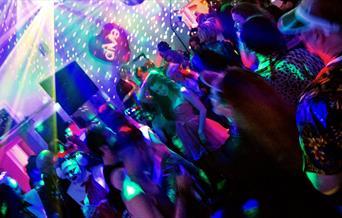 Crowd on a nightclub dancefloor, some people are in fancy dress