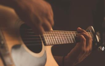 Person playing acoustic guitar with a capo