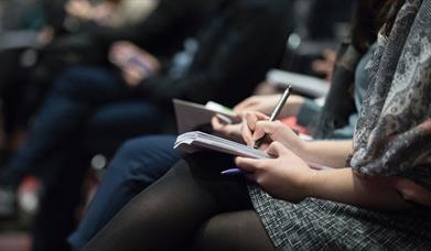 People taking notes at a lecture