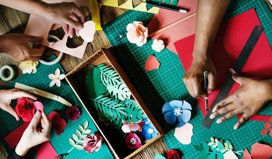 Three people making paper crafts together
